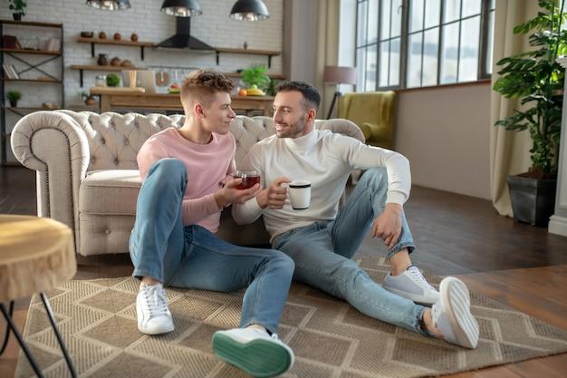 Dwóch mężczyzn z kubkami siedzących obok siebie na podłodze.