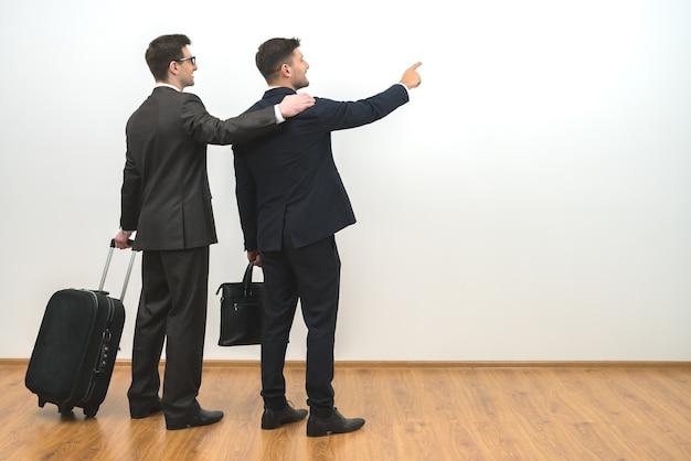 Dwóch mężczyzn z torbami gestykuluje na tle białej ściany