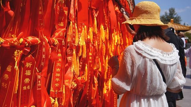 Dwóch międzynarodowych turystów patrzących i czytających kilka wstążek z życzeniami. turyści zawiązali czerwoną wstążkę, chiny