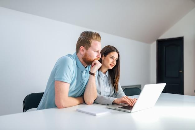 Dwóch millenialnych przedsiębiorców patrząc na ekran laptopa w jasnej sali konferencyjnej.