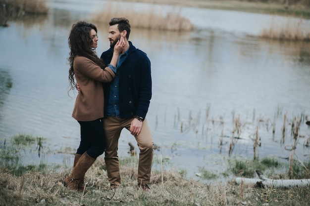 Dwóch miłośników rasy kaukaskiej nad jeziorem. brodaty mężczyzna i zakochana kędzierzawa kobieta. walentynki.