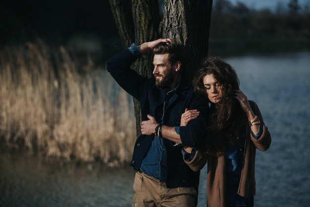 Dwóch miłośników rasy kaukaskiej stoi obok drzewa nad jeziorem. brodaty mężczyzna i zakochana kędzierzawa kobieta. walentynki.