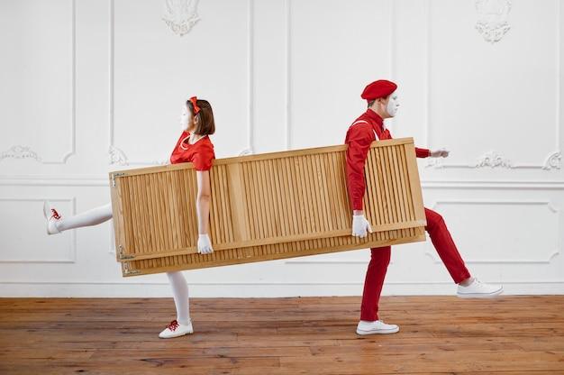 Dwóch mimów, klaunów z drewnianą ścianką działową
