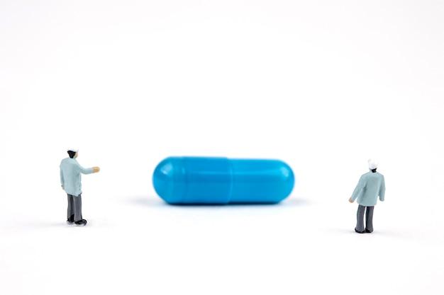 Dwóch miniaturowych lekarzy kontrolujących pigułkę