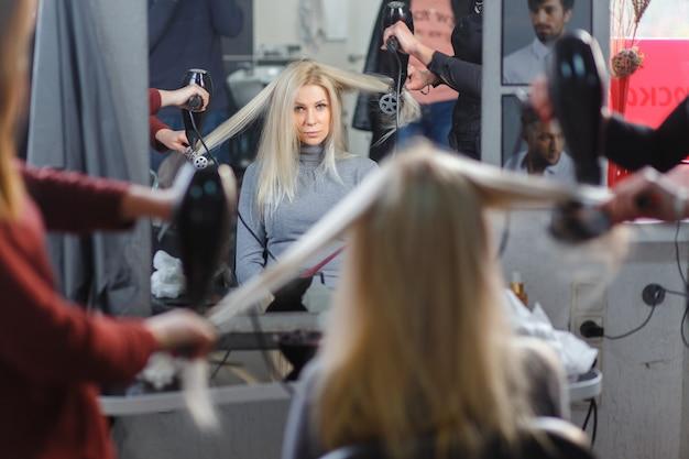 Dwóch mistrzów jednocześnie suszyło suszarką do włosów model blond w gabinecie kosmetycznym. widok z tyłu.