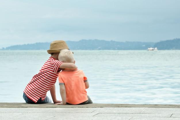 Dwóch młodszych braci siedzi na molo i obejmuje w oddali morze i góry w oddali widok z tyłu