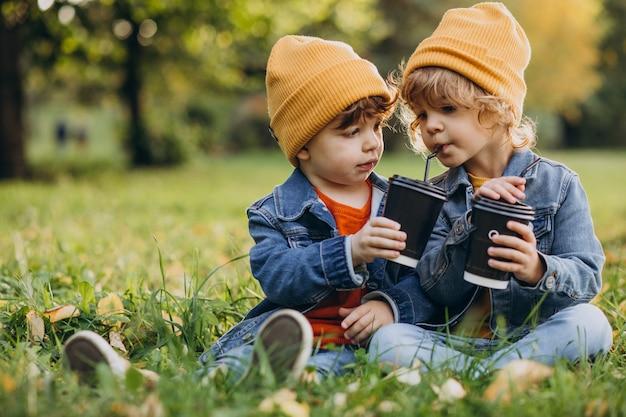 Dwóch młodszych braci siedzi na trawie i pije herbatę