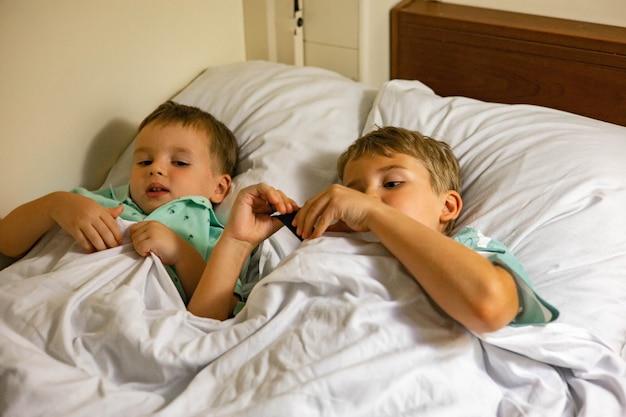 Dwóch młodszych braci śpi na łóżku w luksusowym, wygodnym wagonie kolejowym, ciesząc się podróżą pociągiem