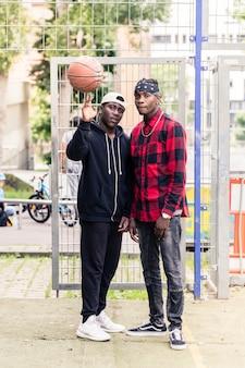 Dwóch młodych afroamerykanów mężczyzn pozowanie na zewnątrz na boisko do koszykówki