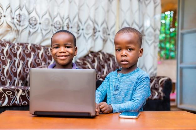 Dwóch młodych afrykańskich braci przy użyciu komputera przenośnego patrząc w kamerę podekscytowany siedzi w domu