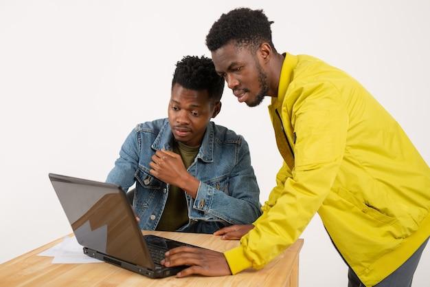 Dwóch młodych afrykańskich mężczyzn przy stole z laptopem