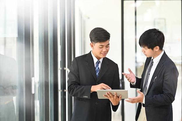 Dwóch młodych biznesmen konsultuje się i rozmawia z rozmowy biznesowej.