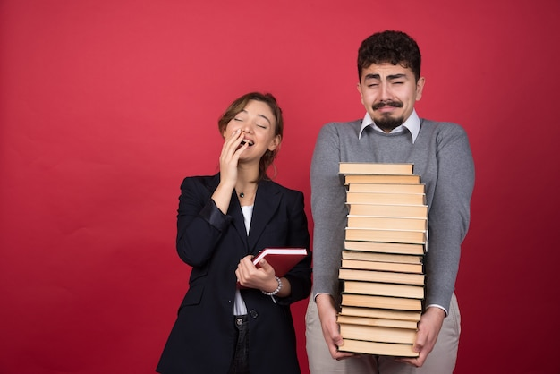 Dwóch młodych biznesmenów czuje się zmęczony z książkami
