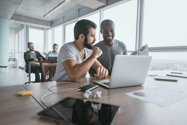 Dwóch młodych biznesmenów korzystających z laptopa i omawiających nowy projekt w biurze, opracowywanie strategii dla biznesu online, wyjaśnianie dzielenia się pomysłami, przygotowywanie prezentacji, przeprowadzanie burzy mózgów