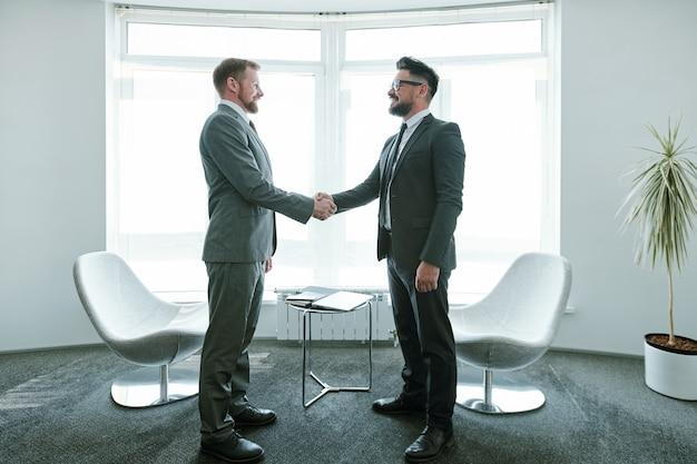 Dwóch młodych biznesmenów, odnoszących sukcesy w garniturach, ściskających dłonie po negocjacjach, stojących przed oknem biura, stołem i fotelami