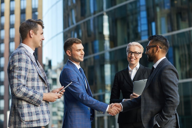 Dwóch młodych biznesmenów ściskających dłonie stojąc wśród swoich kolegów w mieście