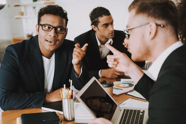 Dwóch młodych biznesmenów spiera się o coś