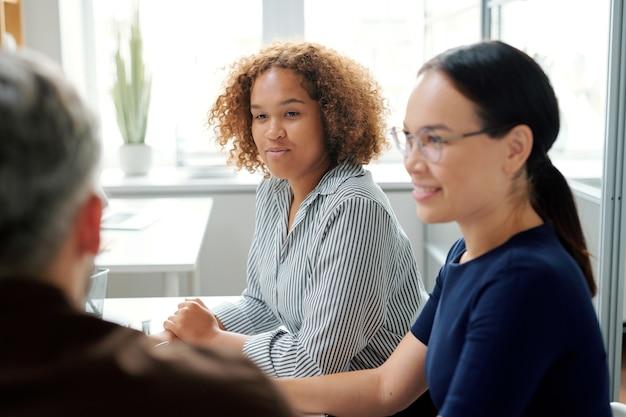 Dwóch młodych biznesmenów wielokulturowych siedzi przy biurku, podczas gdy jeden z nich patrzy na biznesmena i słucha tego, co mówi