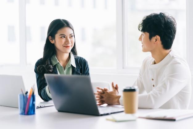 Dwóch młodych biznesmenów z azji rozmawia o projekcie na koniec roku