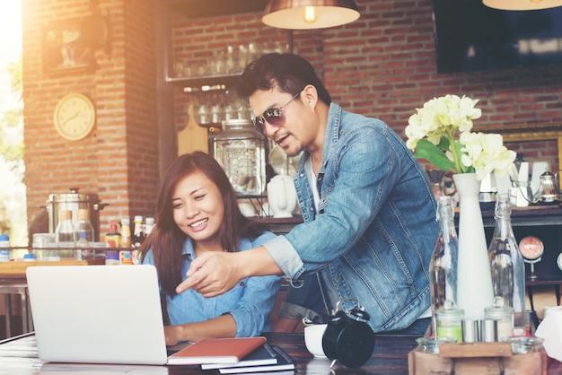 Dwóch młodych biznesowych pracuje na swoim laptopie, siedząc w ac