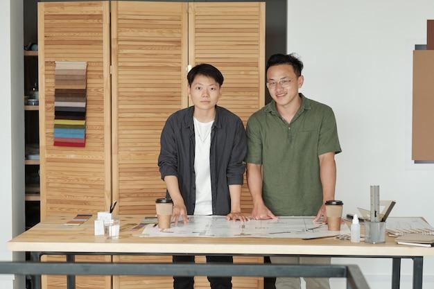 Dwóch młodych chińskich architektów w casualwear pracuje nad szkicem w biurze