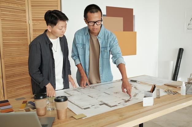 Dwóch młodych chińskich inżynierów omawiających szkic na planie