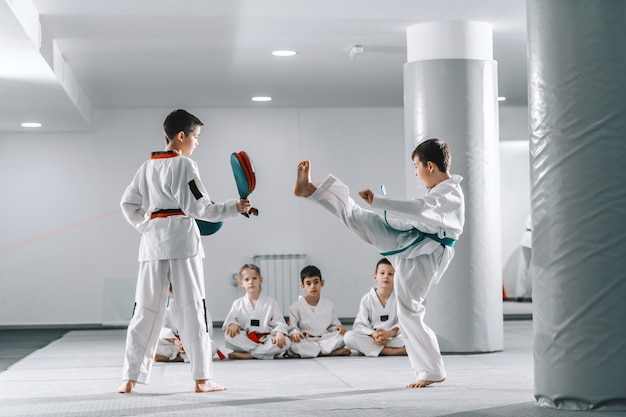 Dwóch młodych chłopców rasy kaukaskiej w doboksach trenujących taekwondo na siłowni. jedna dziewczyna kopie, a druga trzyma cel kopnięcia