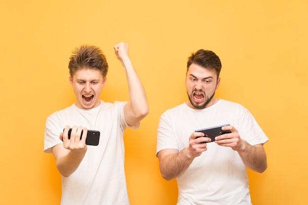 Dwóch młodych chłopców rywalizuje w grze mobilnej, stojąc ze smartfonami w rękach na żółtym tle