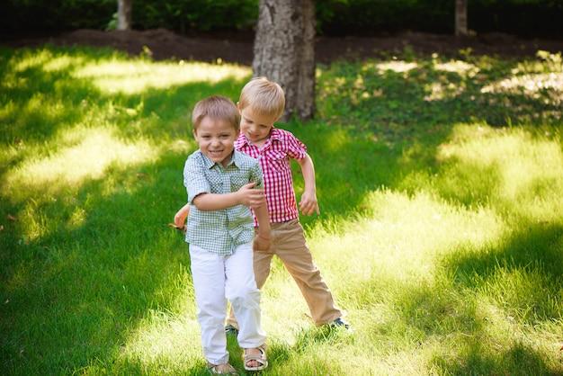 Dwóch młodych chłopców spaceruje i odpoczywa w parku.