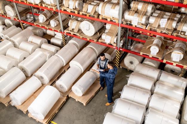 Dwóch młodych ekspertów technicznych w dziedzinie odzieży roboczej omawia momenty pracy na spotkaniu w magazynie swojej fabryki