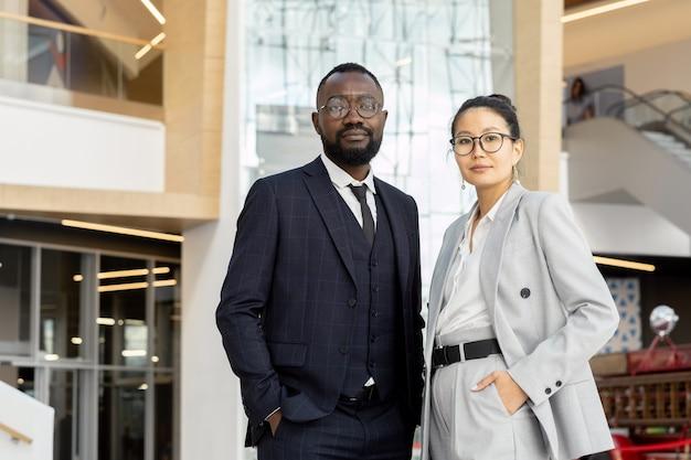 Dwóch młodych eleganckich pracowników w garniturach stojących w dużym centrum biznesowym