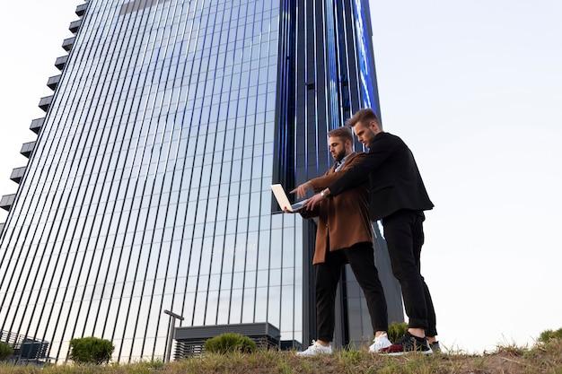 Dwóch młodych facetów omawia swój projekt biznesowy i przegląda informacje na laptopie