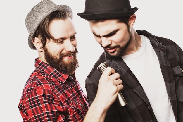 Dwóch młodych facetów śpiewa na biało