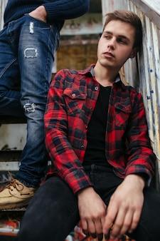 Dwóch młodych facetów stoi w opuszczonym budynku na schodach
