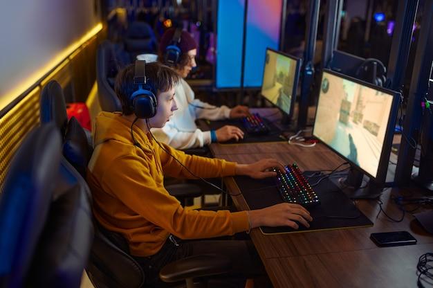 Dwóch młodych graczy w zestawach słuchawkowych gra w klubie gier wideo