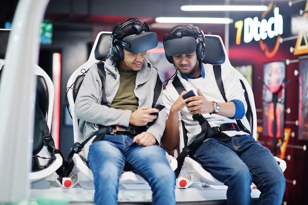 Dwóch młodych hindusów bawi się z nową technologią zestawu słuchawkowego vr w symulatorze rzeczywistości wirtualnej z telefonem komórkowym pod ręką