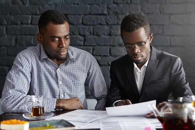 Dwóch młodych kierowników pochodzenia afroamerykańskiego przeglądających sprawozdanie finansowe