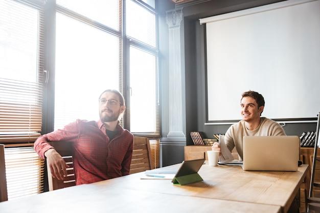 Dwóch młodych kolegów siedzi w biurze