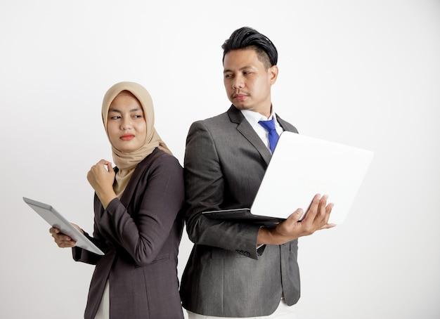 Dwóch młodych kolegów z biznesu niezręcznie dyskutuje i myśli o projektach. z trzymając tablet i laptop na białym tle