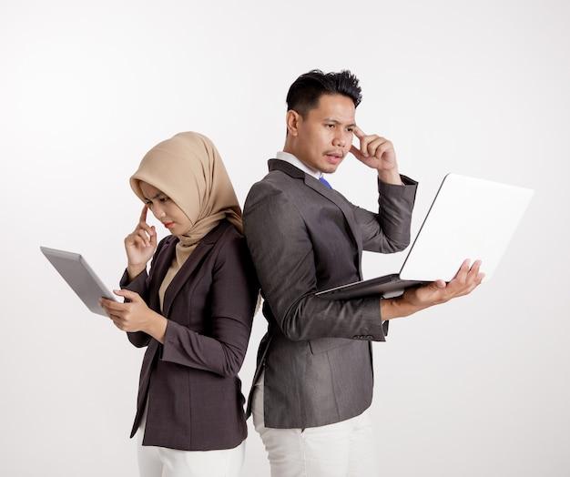 Dwóch młodych kolegów z biznesu omawianie i myślenie projektów dotyczących gadżetów razem na białym tle