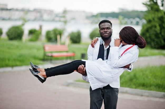 Dwóch młodych lekarzy afroamerykanów para w biały płaszcz. mężczyzna trzymać kobiety na ręce.
