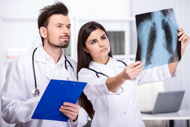 Dwóch młodych lekarzy patrzy na rtg w gabinecie lekarskim.