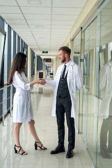 Dwóch młodych lekarzy stażystów pozuje na korytarzu nowoczesnego szpitala. koncepcja zdrowia