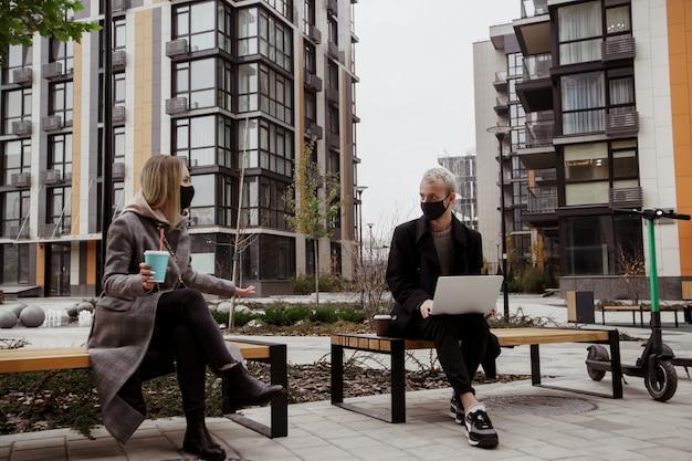 Dwóch młodych ludzi dyskutuje o czymś ciekawym, siedząc na ławkach i zachowując dystans