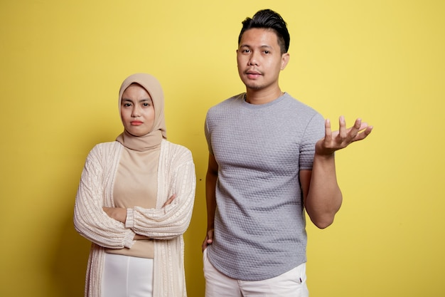 Dwóch młodych ludzi, kobieta w hidżabie i mężczyzna z miną proszącą o coś. pojedynczo na żółtym tle