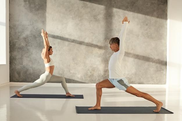 Dwóch młodych ludzi rasy kaukaskiej praktykujących jogę w klubie fitness rano. atrakcyjny wysportowany mężczyzna i blondynka sprawna kobieta robi warrior one lub virabhadrasana 1 na matach w siłowni, stojąc na szachownicy