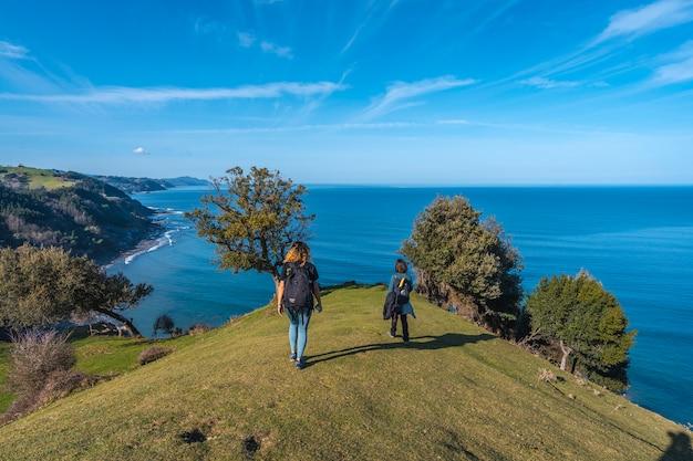 Dwóch młodych ludzi spacerujących wzdłuż pięknego wybrzeża od deba do zumaia
