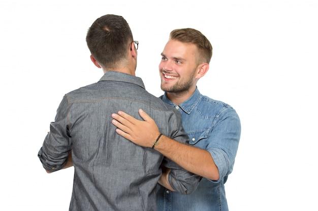 Dwóch młodych ludzi witających się z uśmiechem
