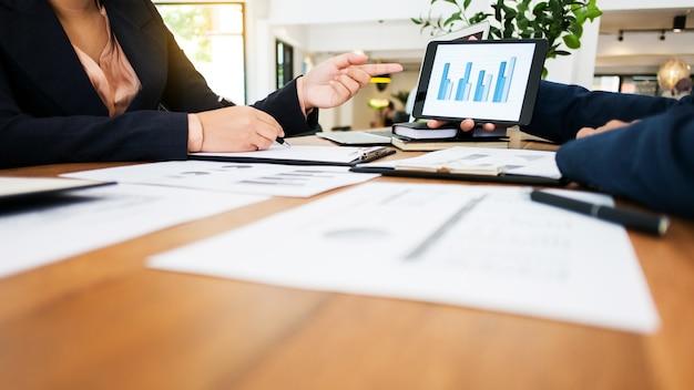 Dwóch młodych menedżerów omawiających partnerów z inwestycjami makroekonomicznymi i giełdowymi