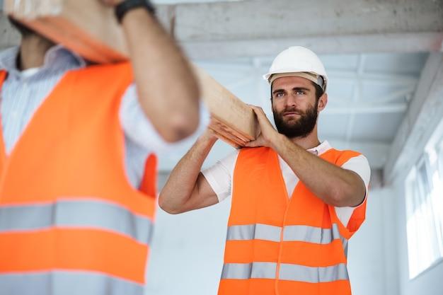 Dwóch młodych mężczyzn budowniczych niosących drewniane deski na budowie z bliska